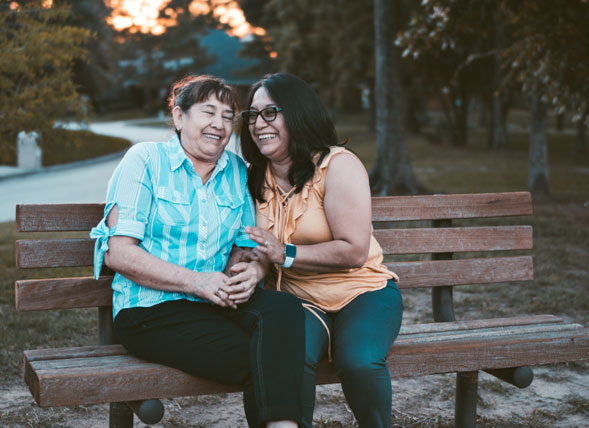 Two Women Smiling while sitting on a bench
